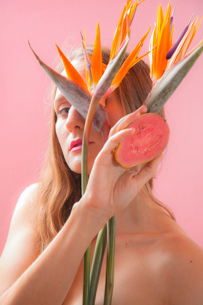 Woman in front of a pink background holding an orange flower and grapefruit
