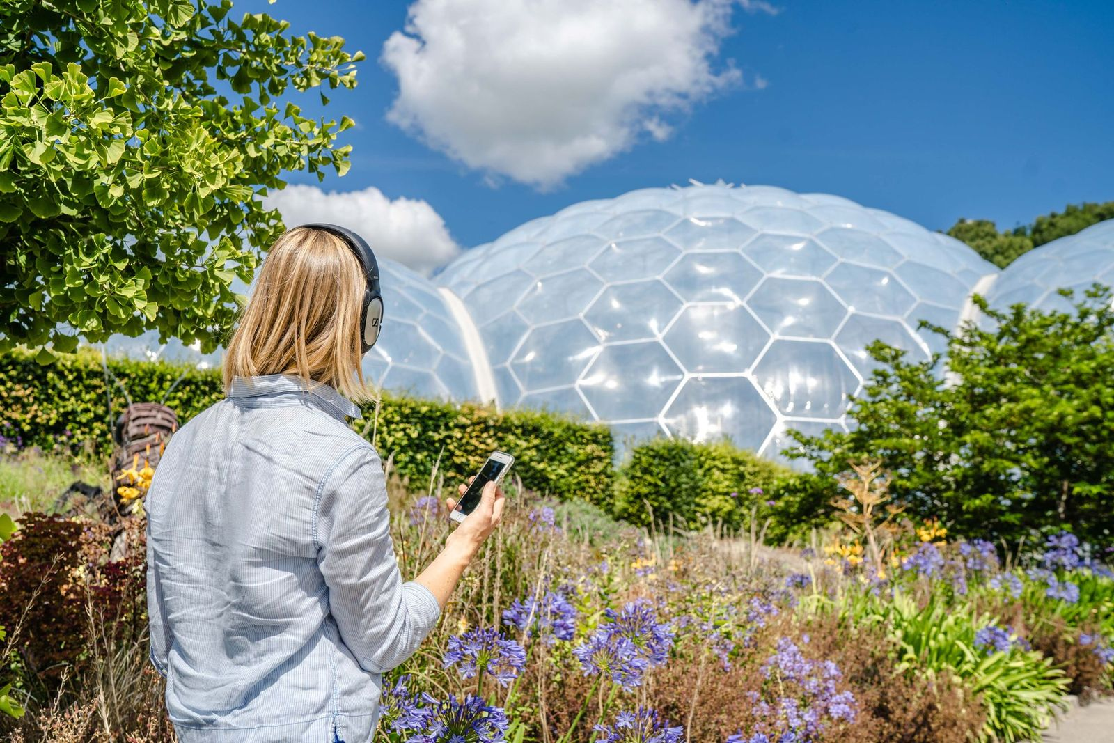 Woman listening to her smart phone through headphones outside the Eden Project domes