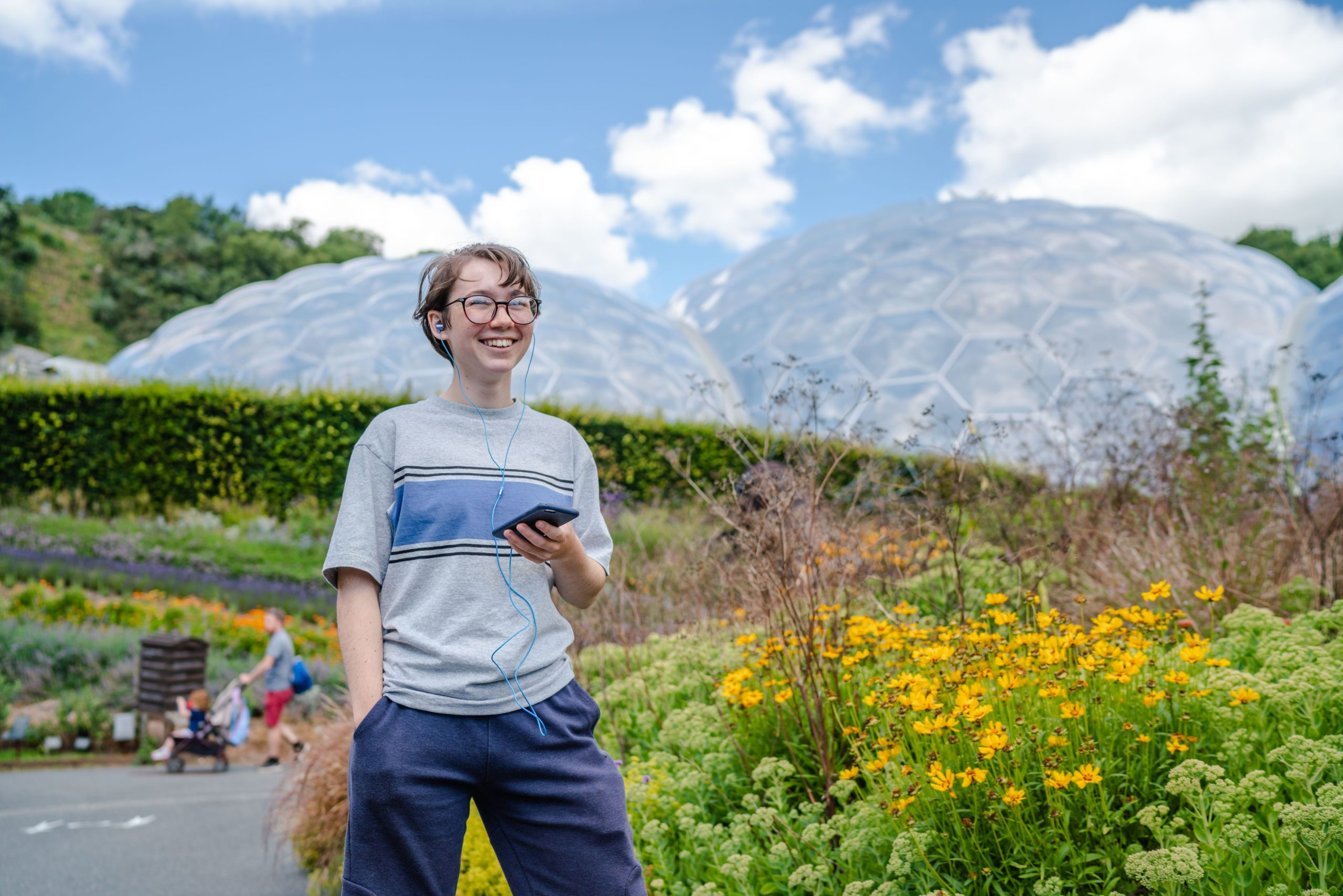 Boy listening to phone through headphones in front of the Eden Project domes