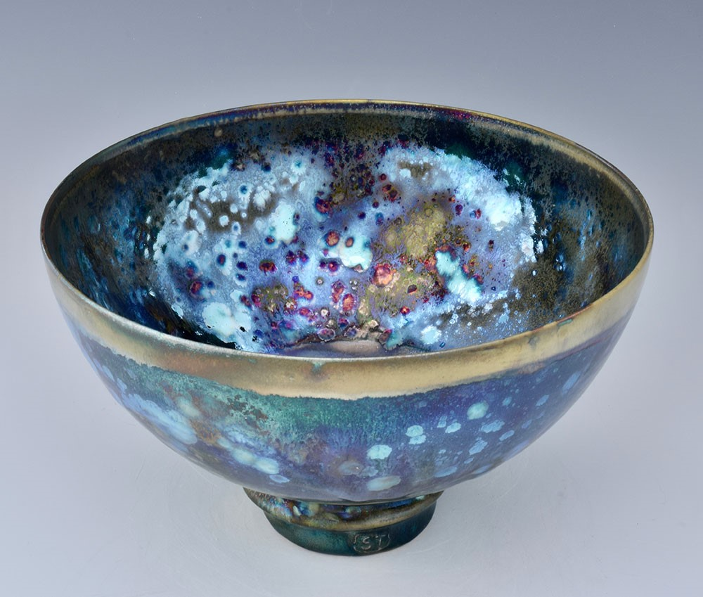Olive, multi-coloured bowl, with a shiny, iridescent finish. Made by Sutton Taylor