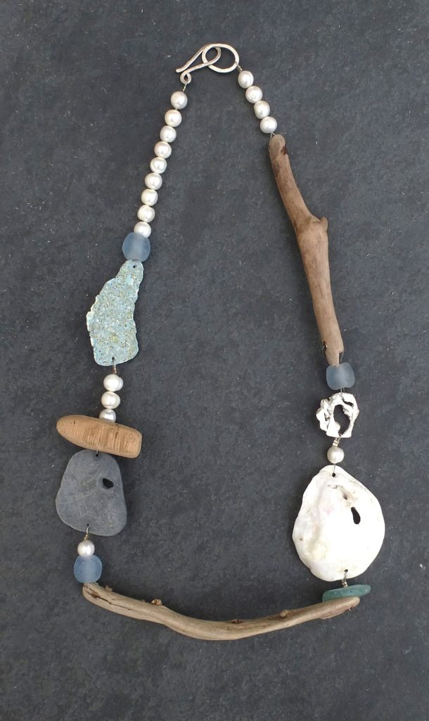 Driftwood and pearl necklace against a dark grey background