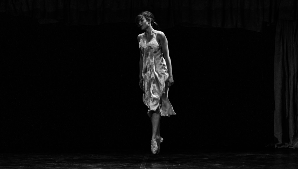 A dancer in a light grey dress against a black background. The photo is taken mid jump, so she looks as though she is suspended in the air.
