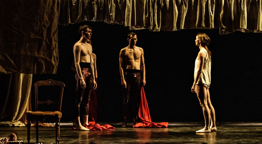Three male dancers stand in the triangle, facing in towards each other