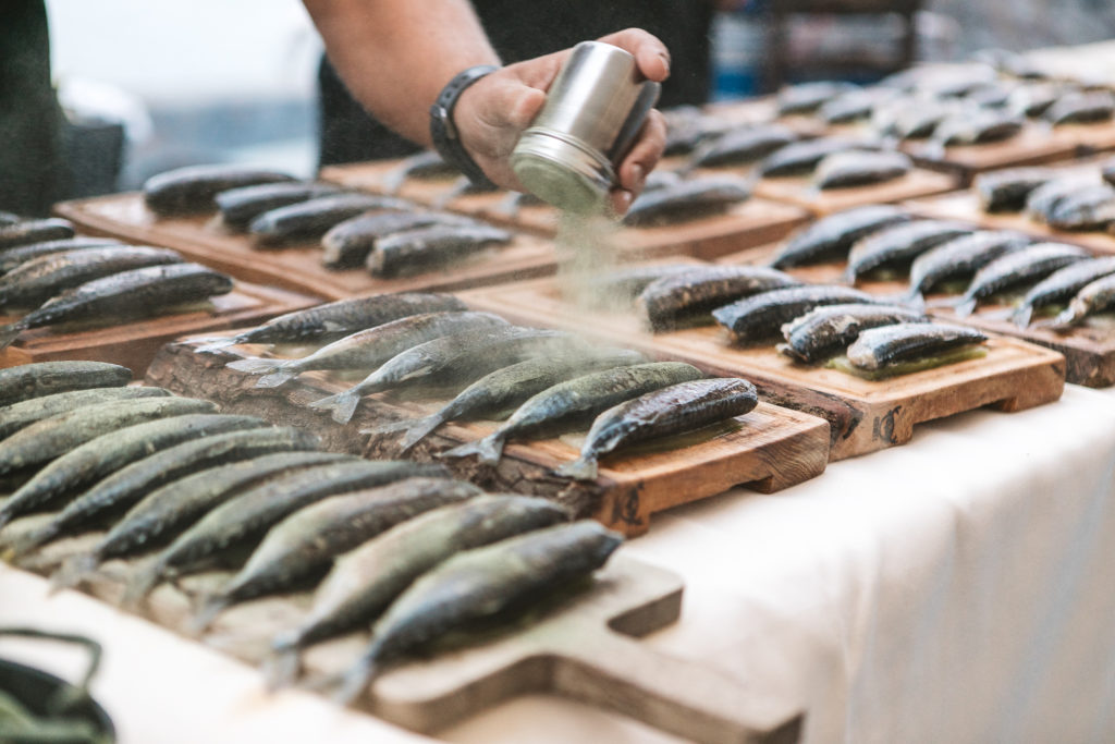 Someone dusts whole fish with some kind seasoning. The fish are lined up on wooden boards.