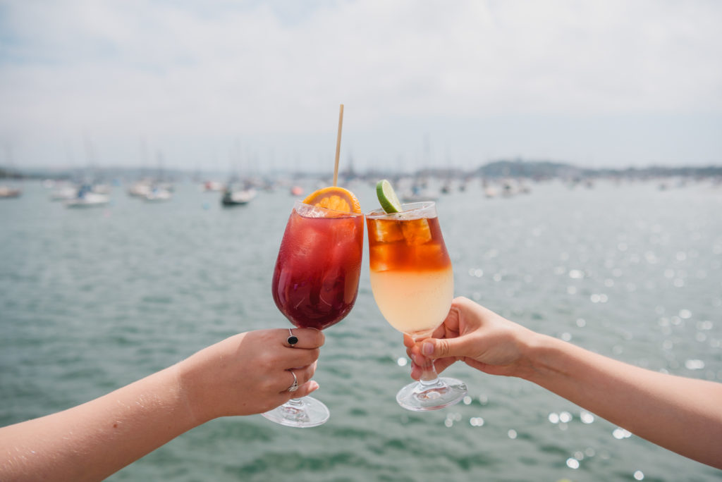Two people, off camera, are clinking two orange cocktails together. We see their arms and hands, and the blue glittering sea behind them.
