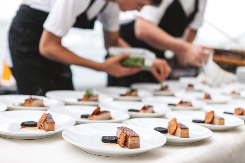 A table is filled with white plates, being dressed for service.