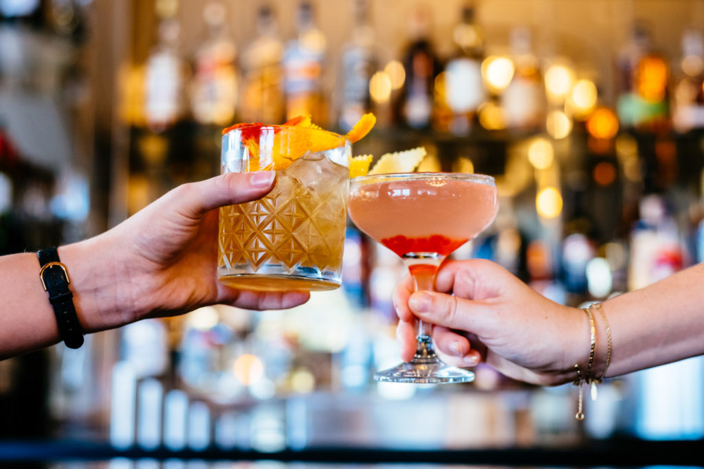 Two people, off camera, are clinking two brightly coloured cocktails together.