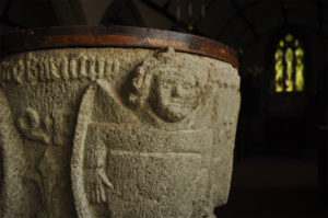 A stone font with a face carved into it