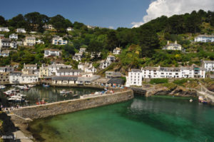 The village of Polperro. White houses on the cliffs overlooking the blue, green sea and the harbour.