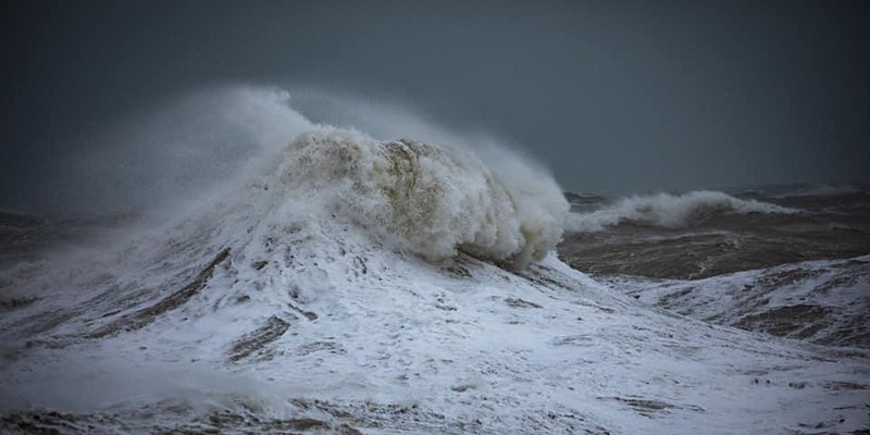A stormy sea, with a big white wave crashing with sea spray.