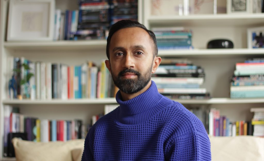 A headshot of Hetain Patel. He is wearing a rich purple roll neck jumper, and is looking into the camera. Behind him is an out of focus book shelf.