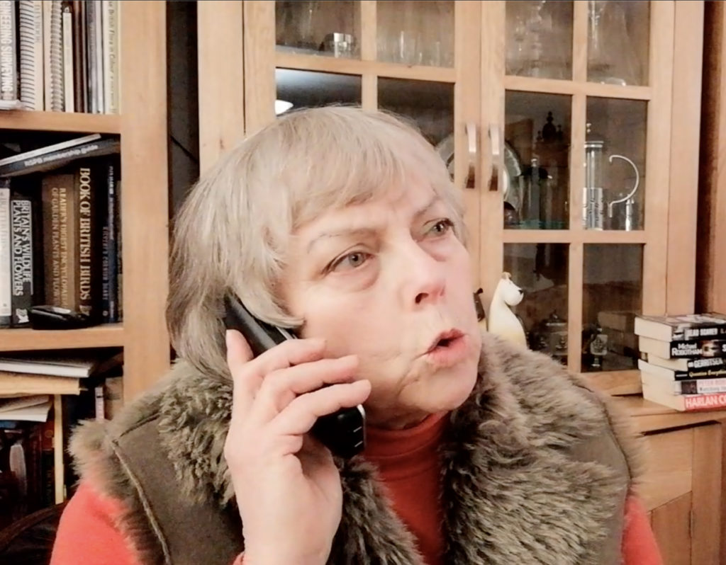 A woman is speaking on the phone, she is wearing a brown fur scarf and a red roll neck jumper.