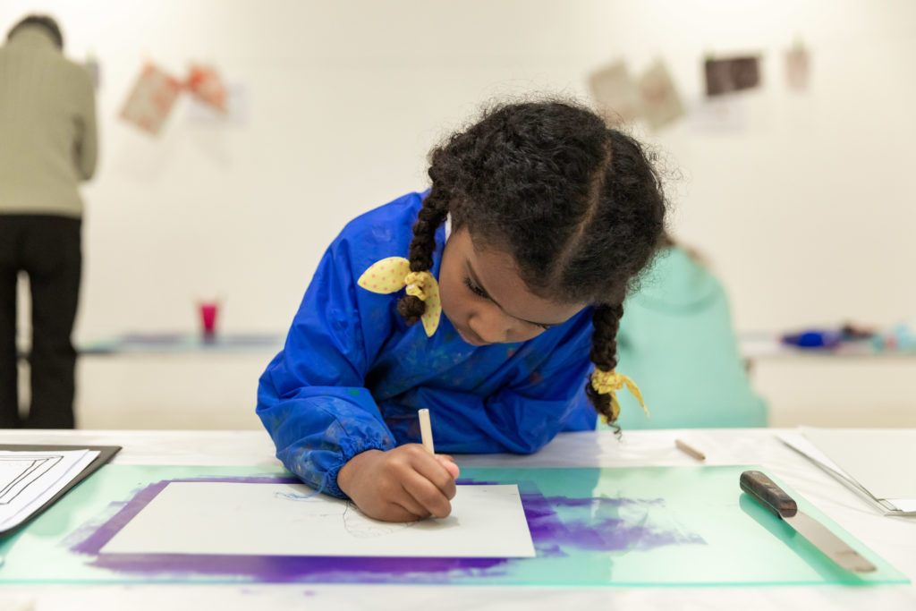 A little girl is drawing on a piece of paper in an art gallery. She has her head down in concentration and is wearing bright blue overalls, and has yellow ribbons in her braided hair.