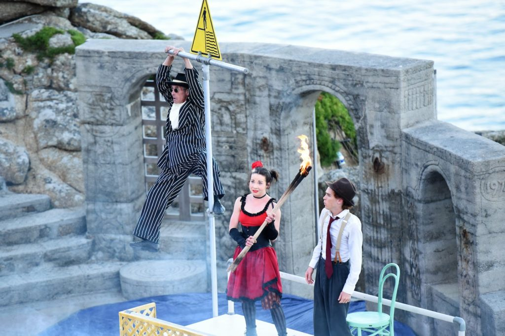 A man hanging from a scaffolding pole on stage. Below is a woman holding a flaming torch, and a man looking up at him.
