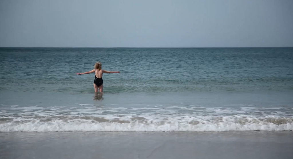 A woman is standing in the sea with her arms stretched out either side of her. It's a sunny day and the water is calm.