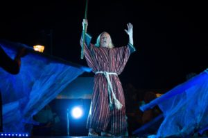 A man dressed in a striped robe raises his hands to the sky