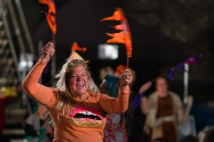 A woman in an orange top dances holding orange flags